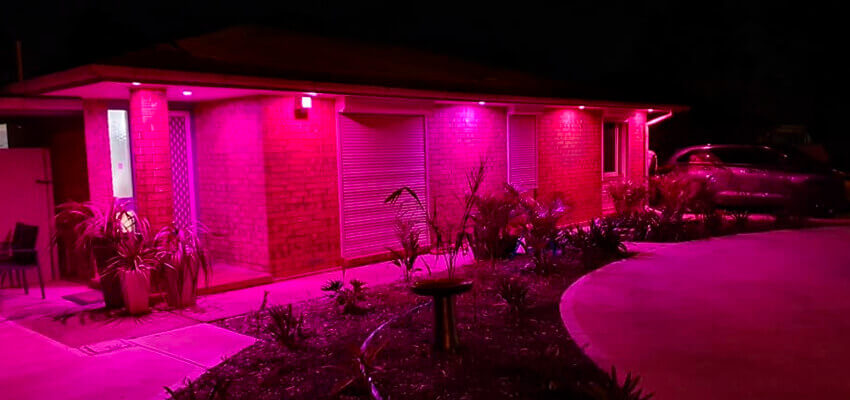 Golden Grove Electrical and Data Services. Upgrade to LED lighting blog pic of front of family home at night with pink lights under eaves.